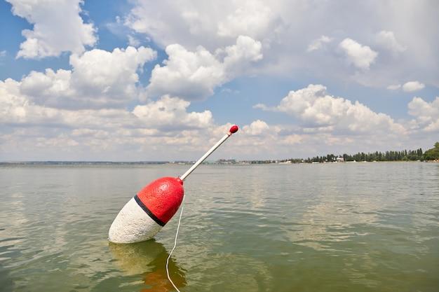 Duży pływak unosi się na spokojnej powierzchni jeziora, czekając na ukąszenie