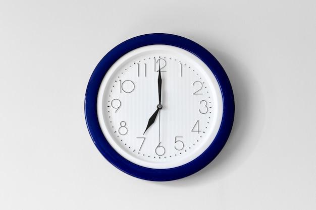 Duży pojedynczy okrągły zegar biurowy pokazujący siódmą godzinę