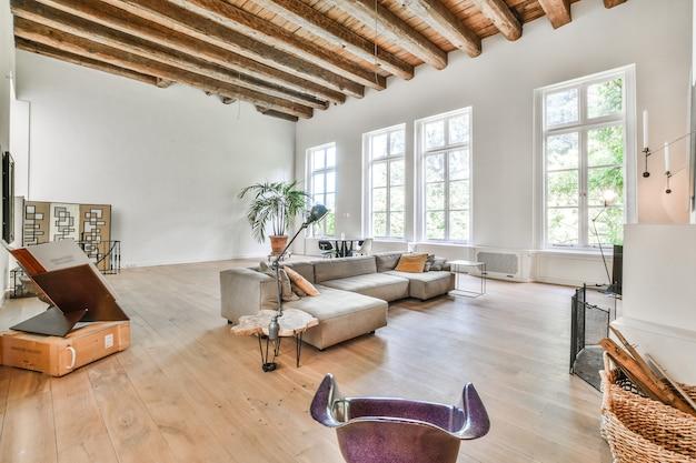 Duży pokój z wysokimi drewnianymi belkami stropowymi, wyposażony w szarą kanapę i designerskie elementy w minimalistycznym stylu