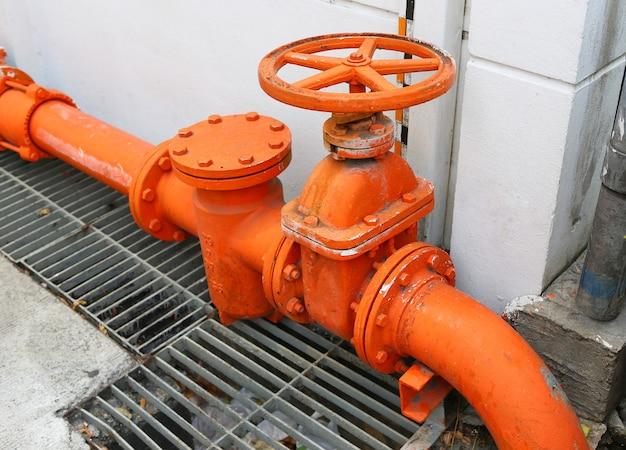 Duży pomarańczowy rurociąg główny zaopatrzony w wodę z zaworem odcinającym na betonowej ścianie.