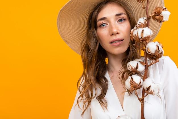 Duży portret tajemniczej dziewczyny w średnim wieku w pomarańczowym kapeluszu, delikatnie trzyma w dłoniach naturalną bawełnę