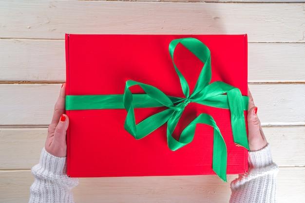 Duży prezent na boże narodzenie w ręce kobiety. duże czerwone pudełko na prezent na boże narodzenie z świąteczną zieloną wstążką, ręce dziewczyny na zdjęciach, widok z góry na podłoże drewniane