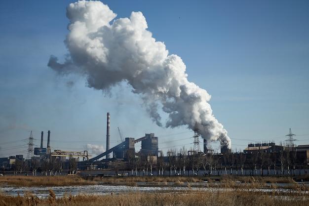 Duży przemysłowy zakład metalurgiczno-chemiczny w mariupolu na ukrainie fabryka zanieczyszcza środowisko katastrofa ekologiczna toksyczne kominy przedsiębiorstwa rury na tle nieba z powierzchni wydzielają dym
