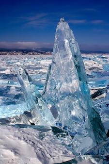 Duży przezroczysty kawałek lodu stoi pionowo na jeziorze bajkał