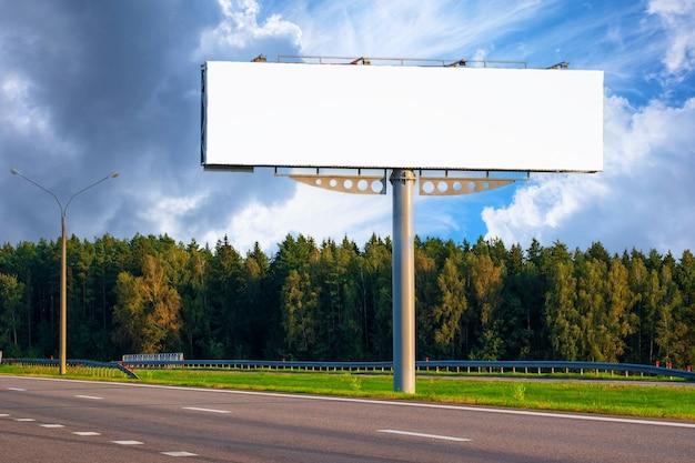 Duży pusty makieta billboard wzdłuż autostrady z lasem na tle błękitnego nieba z pięknymi chmurami.