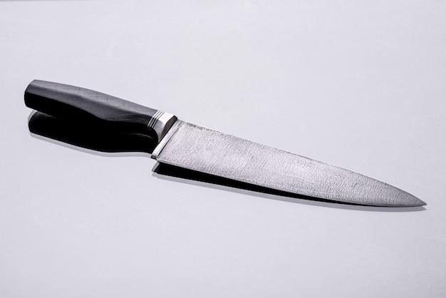 Duży, ręcznie robiony nóż myśliwski leżący na ciemnym, monotonnym tle