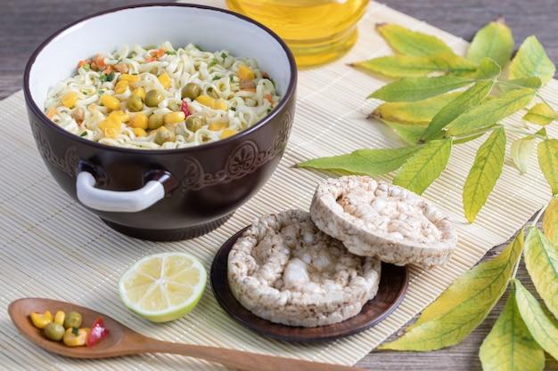 Duży rondel pysznego makaronu z kukurydzą, groszkiem i okrągłą skórką od chleba
