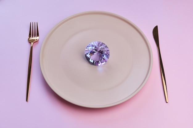Duży różowy diamentowy kamień na talerzu z nożem i widelcem.