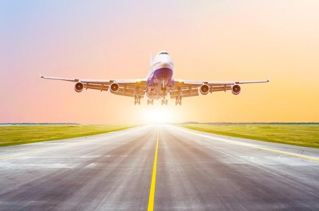 Duży samolot pasażerski startuje z pasa startowego przed światłem słonecznym.
