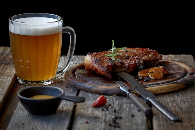 Duży smażony stek, szklanka piwa, musztarda i sztućce na starym drewnianym blacie