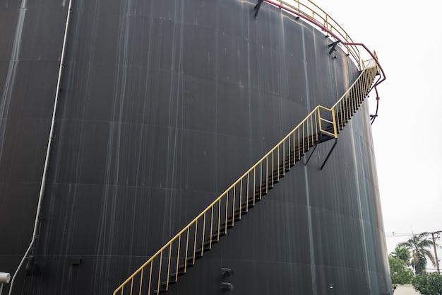 Duży stary zardzewiały zbiornik na olej czarny ze schodami