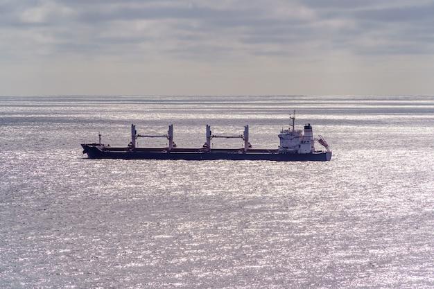 Duży statek przemysłowy płynący w oddali ze srebrnymi falami od słońca i horyzontu z chmurami w tle. hiszpania.