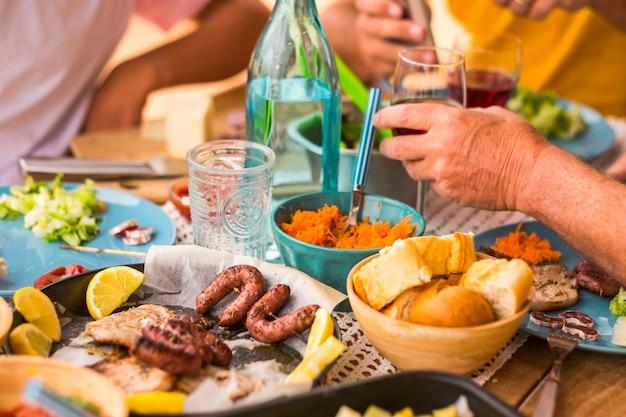 Duży stół pełen jedzenia, chleba, mięsa, warzyw... - niektórzy ludzie siedzący przy stole jedzący i pijący wino i wodę - świętowanie - dużo sałatek i wszelkiego rodzaju jedzenia