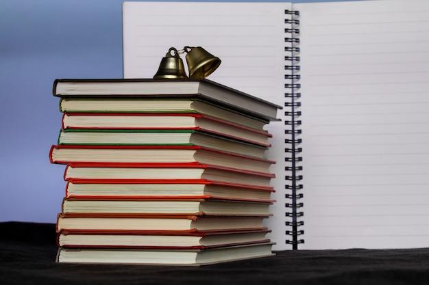 Duży stos książek z otwartym notatnikiem w tle