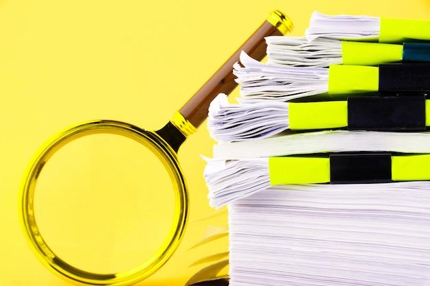 Duży stos niedokończonych dokumentów czekających na weryfikację, szkło powiększające, na żółtym tle. koncepcja biznesu i edukacji. skopiuj miejsce