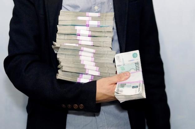 Duży stos papierowych pieniędzy w ręku biznesmena dorosłych. pojęcie sukcesu finansowego. dużo pieniędzy w męskich rękach