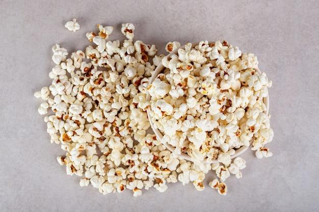 Duży stos popcornu całkowicie zakrywający miskę na marmurze.