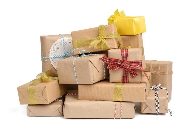 Duży stos prezentów zawiniętych w brązowy papier pakowy i przewiązanych jedwabną wstążką