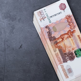 Duży stos rosyjskich banknotów pieniężnych o wartości pięciu tysięcy rubli leżących na szarej cementu