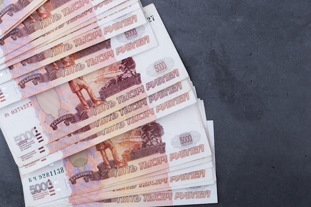 Duży stos rosyjskich banknotów pieniężnych o wartości pięciu tysięcy rubli leżących na szarym cemencie.