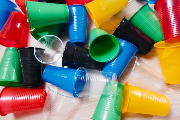 Duży stos wielobarwnych plastikowych kubków porozrzucanych na podłodze. zanieczyszczenia środowiska przez odpady ludzkie