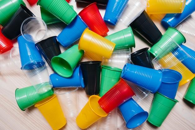 Duży stos wielobarwnych plastikowych kubków porozrzucanych na podłodze. zanieczyszczenia środowiska przez odpady ludzkie.