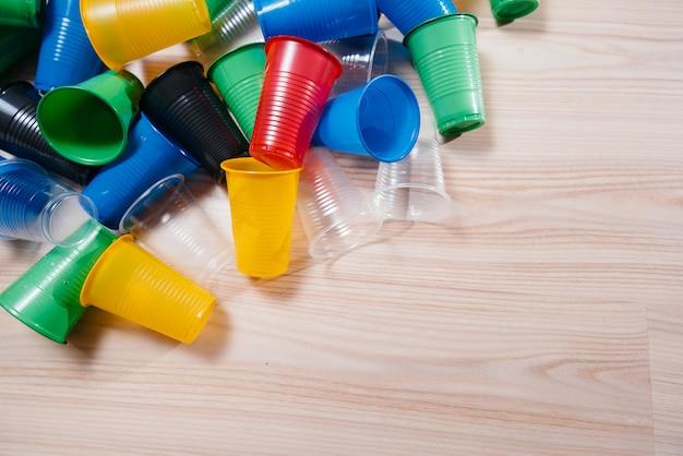 Duży stos wielokolorowych plastikowych kubków rozrzucony na podłodze z wolną przestrzenią. zanieczyszczenia środowiska przez odpady ludzkie
