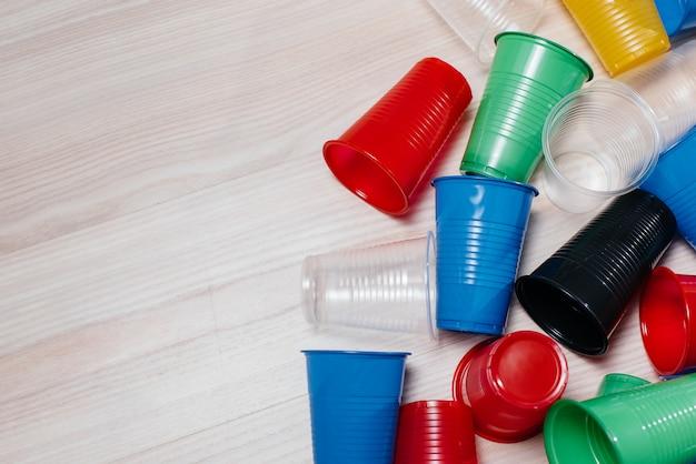 Duży stos wielokolorowych plastikowych kubków rozrzucony na podłodze z wolną przestrzenią. zanieczyszczenia środowiska przez odpady ludzkie.