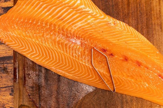 Duży, surowy filet z łososia na drewnianej desce ze szczypcami do rybich kości