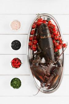 Duży surowy homar w talerzu na stole przed gotowaniem