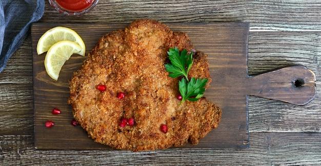 Duży sznycel wiedeński na drewnianej powierzchni. danie mięsne. widok z góry, leżał płasko.