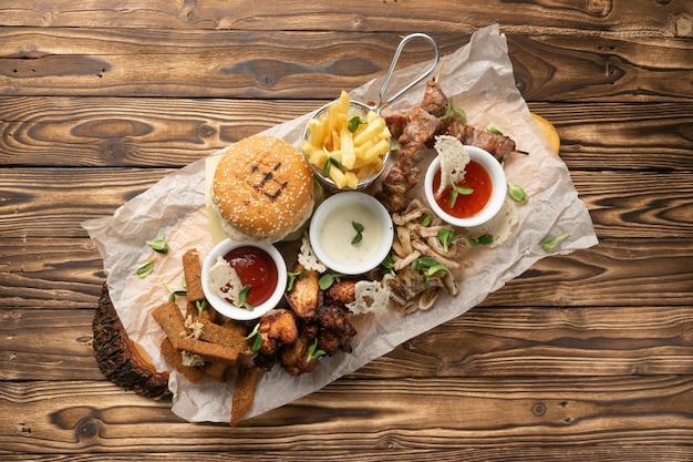 Duży talerz przekąsek do piwa. burger, frytki, szaszłyki wieprzowe i drobiowe, uszy wieprzowe gotowane, bułka żytnia z czosnkiem i trzy rodzaje sosów.