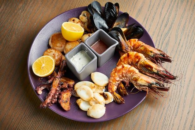 Duży talerz smażonych owoców morza - kalmary, ośmiornice, małże, przegrzebki, krewetki. asortowany owoce morza na ceramicznym talerzu na drewnianej powierzchni. efekt filmowy podczas postu. nieostrość