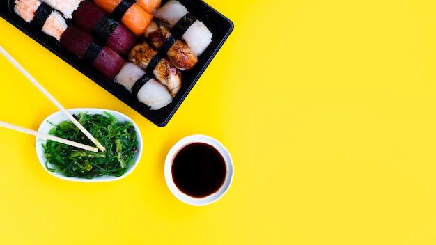 Duży talerz sushi z sałatką z wodorostów i sosem sojowym