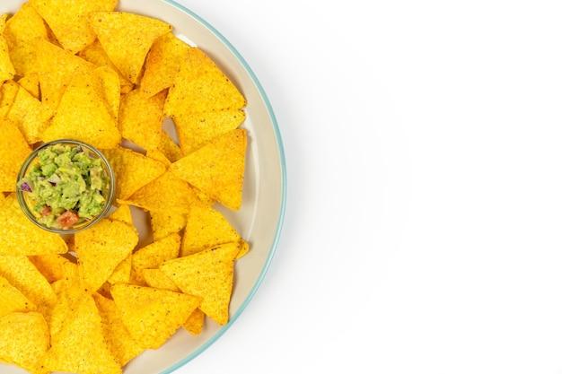 Duży talerz z chrupiącymi nachos i chipsami guacamole na środku dania na białym talerzu z