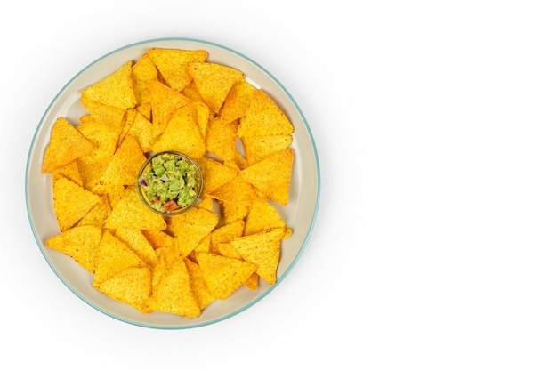 Duży talerz z chrupiącymi nachos i chipsami guacamole na środku dania na białym talerzu