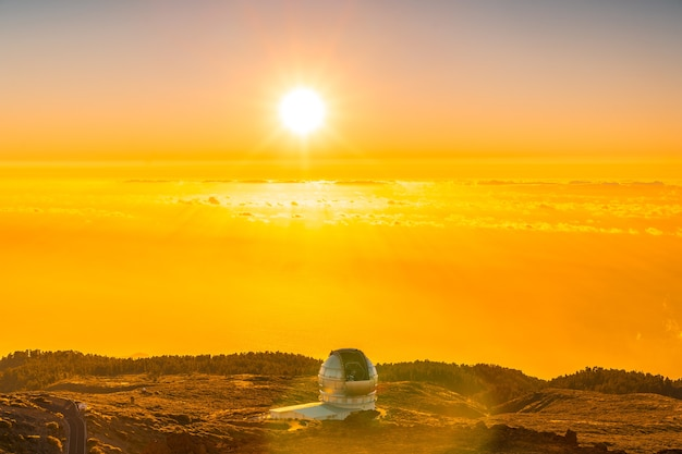 Duży teleskop kanaryjski zwany grantecan optico del roque de los muchachos na caldera de taburiente w pięknym pomarańczowym zachodzie słońca, la palma, wyspy kanaryjskie. hiszpania