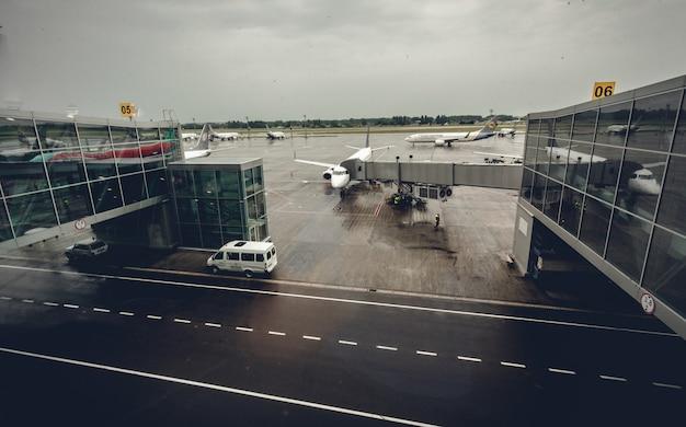 Duży terminal lotniczy z samolotami przy bramkach wejściowych w deszczowy dzień?