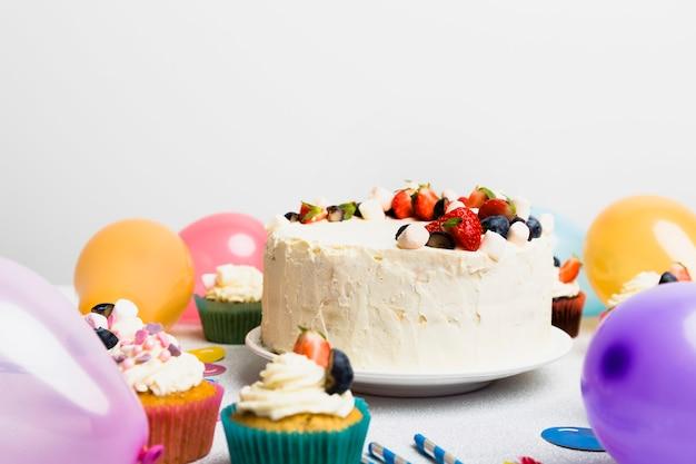Duży tort z różnymi jagodami blisko lotniczych balonów
