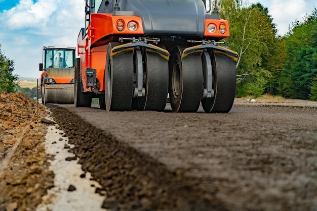 Duży widok na walce drogowe pracujące na budowie nowej drogi