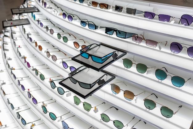 Duży wybór elementów optycznych umieszczonych na składanym białym stojaku z różnymi okularami przeciwsłonecznymi o różnych kształtach.
