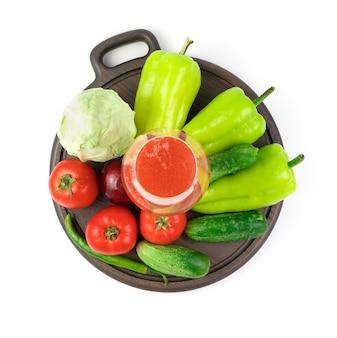 Duży wybór warzyw i szklanka świeżo wyciskanego soku warzywnego na okrągłej tacy. pojęcie prawidłowego odżywiania.