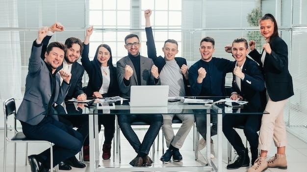 Duży zespół biznesowy pokazujący swój sukces siedząc przy biurku. pojęcie pracy zespołowej