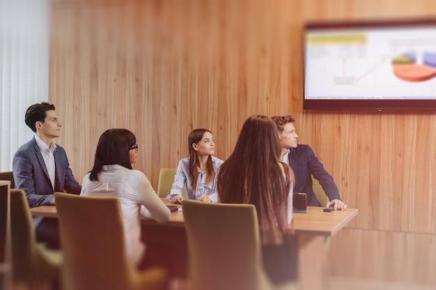 Duży zespół ludzi pracuje przy jednym stole dla laptopów, tabletów i papierów, na tle dużego telewizora na drewnianej ścianie