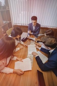 Duży zespół ludzi pracuje przy jednym stole dla laptopów, tabletów i papierów