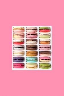Duży zestaw kolorowych makaroników lub makaroników o zróżnicowanych smakach na różowym tle.