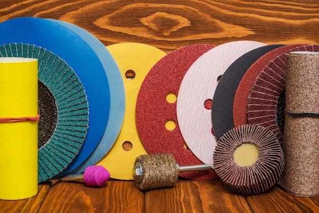 Duży zestaw narzędzi ściernych i wielobarwny papier ścierny na drewnianym tle vintage, kreator służy do szlifowania przedmiotów