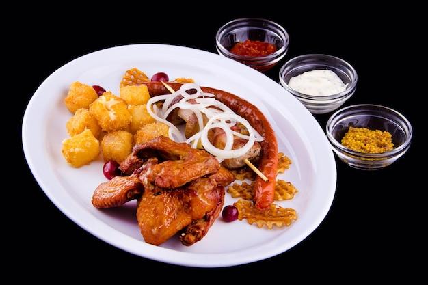 Duży zestaw piwny smażonych przekąsek - skrzydełka kurczaka, szaszłyk wieprzowy, domowe kiełbaski, chipsy ziemniaczane, ser smażony w głębokim tłuszczu, cebula, trzy sosy: biały, czerwony, musztardowy.