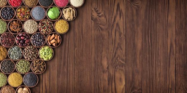 Duży zestaw przypraw na drewnianym stole, widok z góry