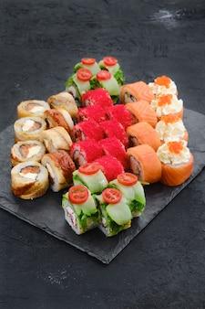 Duży zestaw rolad z krewetkami, łososiem, węgorzem, tuńczykiem i ikrą latającej ryby na talerzu łupkowym